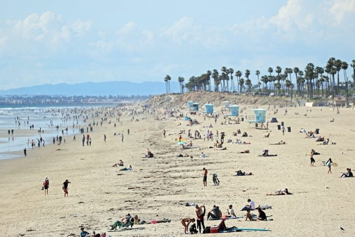 Packed California beaches prompt stricter virus measures