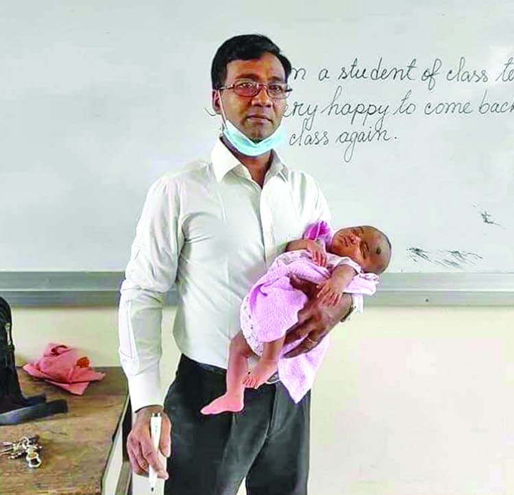 Teacher takes class holding student's baby in his lap