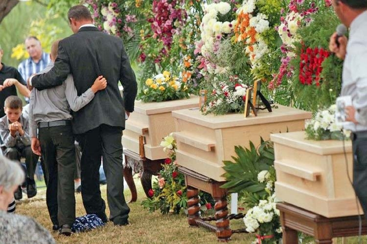 7-month-old twins buried in rain-swept funeral