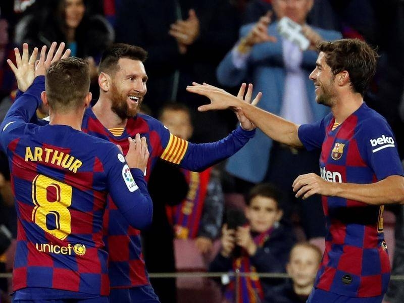 Messi hat-trick sends Barcelona top of La Liga